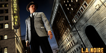 A man dressed in a suit and hat stands, looking down at the ground, holding a gun
