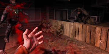 A first=person view, with the player's character's hand seen on screen