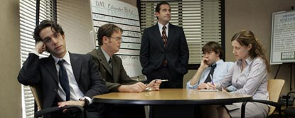 Michael Scott Stood At A White Board With Jim Halpert, Dwight Schrute, Ryan Howard And Pam Beesly Sat Round A Desk