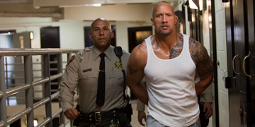 Driver Played By Dwayne Johnson Being Led Through Prison By A Guard