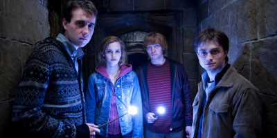 Neville, Hermione, Ron And Harry Stood In A corridor With Lit Wands