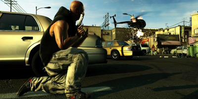 A player, crouching behind a car as a helicopter gets shot down in the background