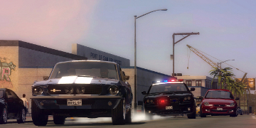 A police chase, led by a greay & white muscle car