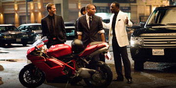 John Rahway, Jesse Attica And Gordon Cozier Stood In A Car Park Infront Of A Red Motorbike