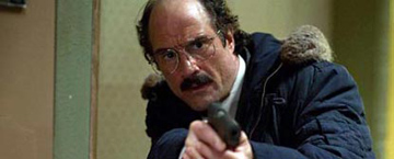 A Polceman Holding His Gun Up Ready To Shoot