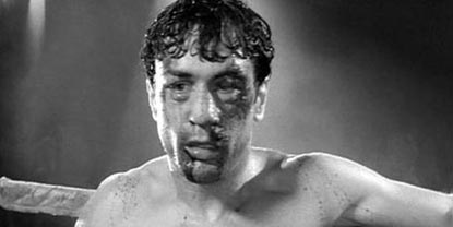 Jake La Motta Played By Robert De Niro, With Blood Over His Face Leaning On Ropes