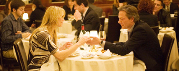 Twom People Sat Across A Dinner Table Holding Hands