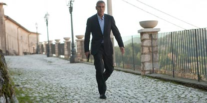 Jack Played By George Clooney, Walking Down A Path Holding A Gun