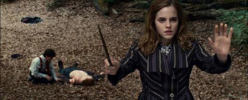 Hermione Casting A Spell Whilst Ron Lies On The Floor With Harry Knelt At His Side In The Background