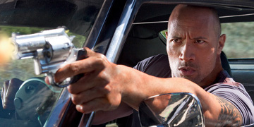 Driver Played By Dwayne Johnson Firing A Gun Out Of His Car Window