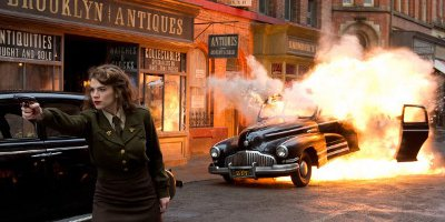Peggy Carter Aiming Her Gun With A Car Explosion In The Background