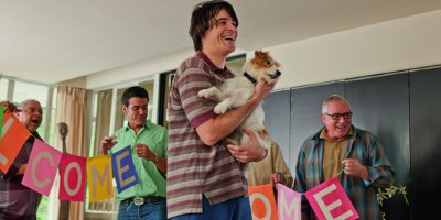 Andy Holding A Dog With People Putting A Welcome Banner Up Behind