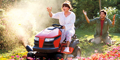Jill Riding Lawnmower Over Flowers