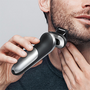 man shaving his beard with shaver