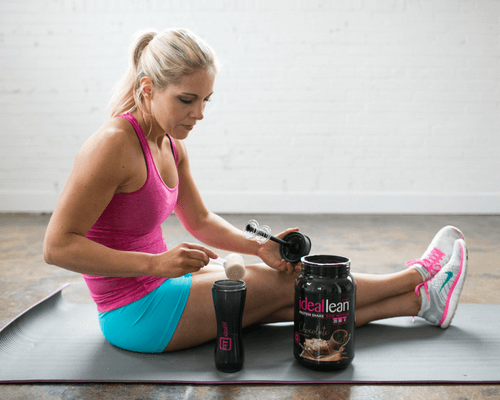 A woman using protein powder to build lean muscle at the gym.