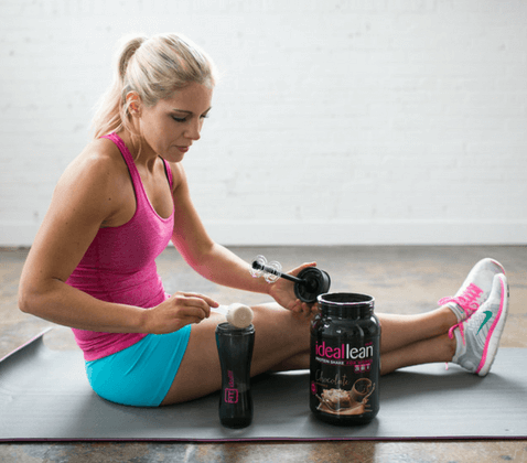 A woman using protein powder after a workout.