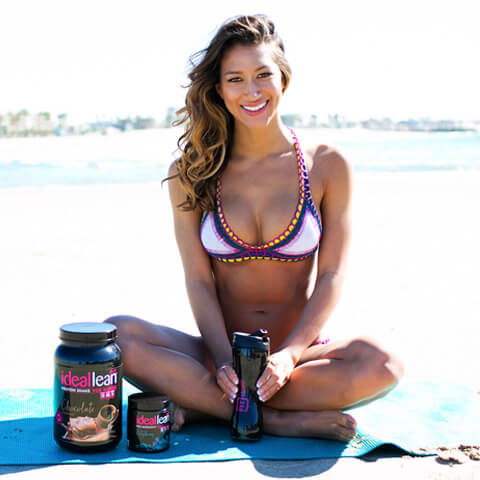 Karina sitting on the beach with IdealFit shaker