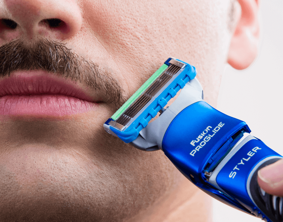 Man trimming moustache with Gillette Styler.