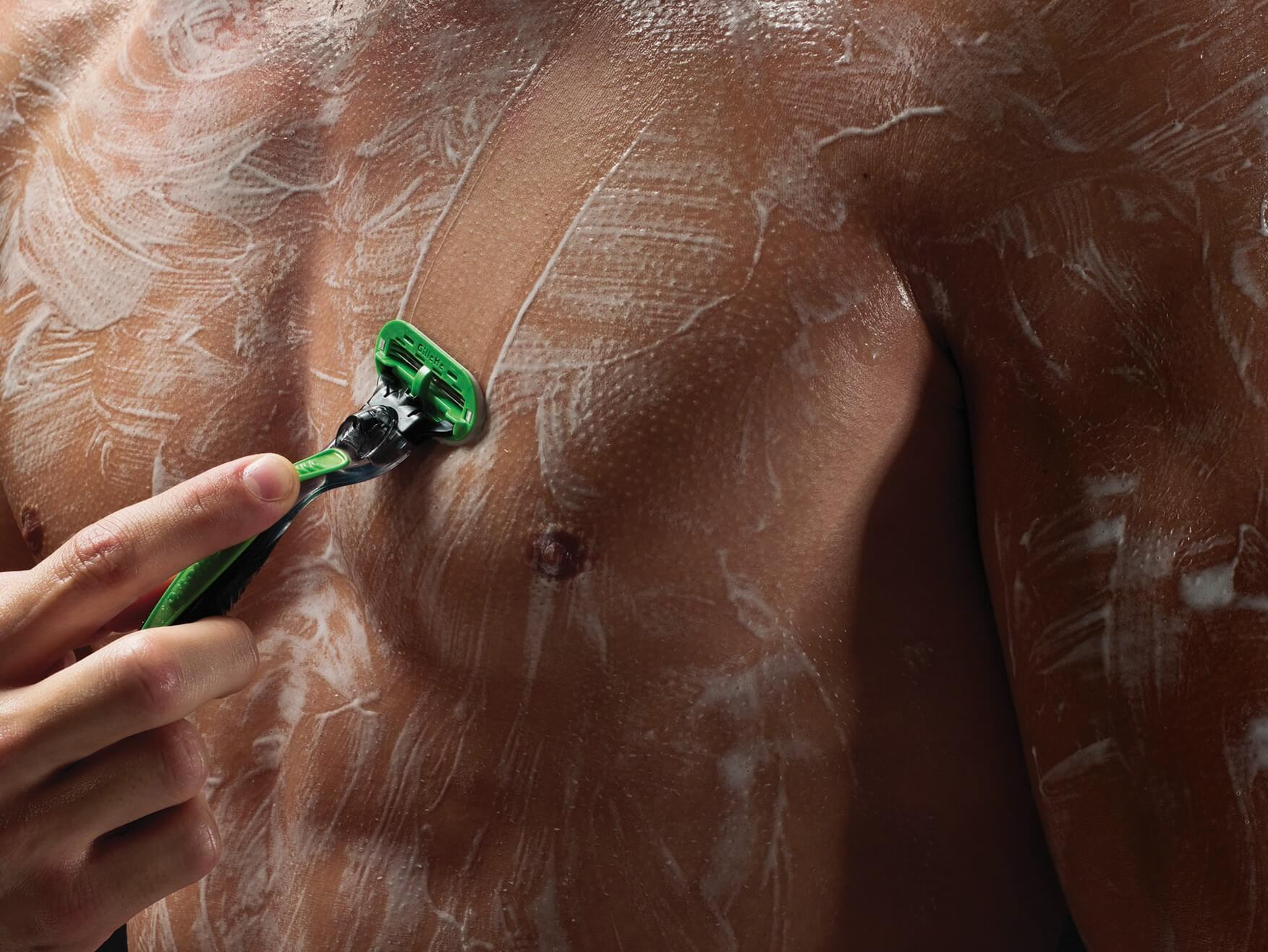 Man shaving chest with Gillette razor.