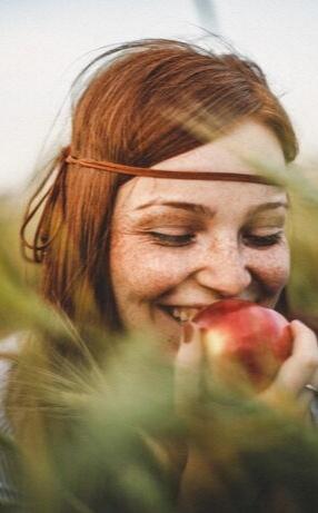 Image d'une fille dans un champ avec une pomme