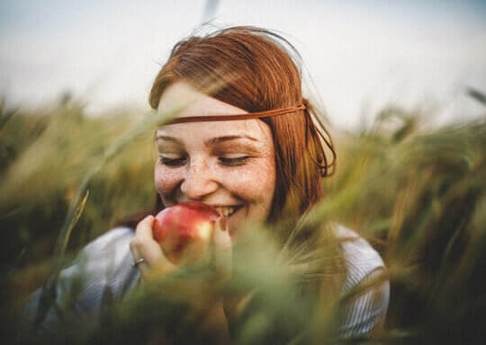 Une femme qui mange une pomme rouge dans un champ