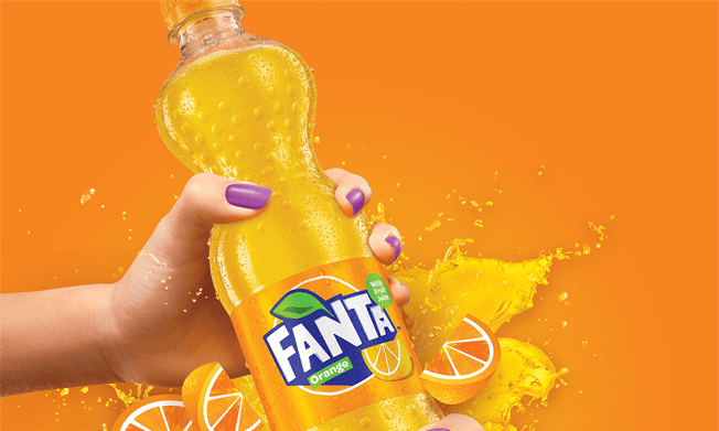 Bottle of Fanta surrounded by slices of orange