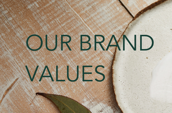 Our brand values text on background banner image of plate with swatch of moisturiser on it.