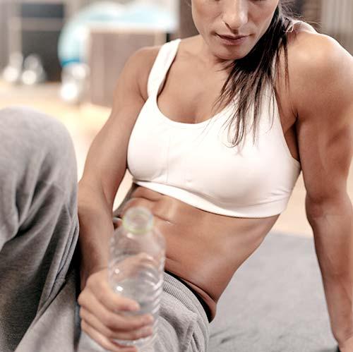 Vrouwelijke atleet rusten in de sportschool met een fles water