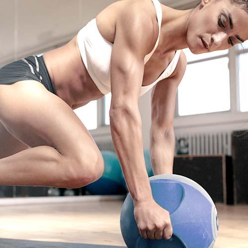 Afgezwakt vrouwelijke atleet die zich uitstrekt met medicijnen bal