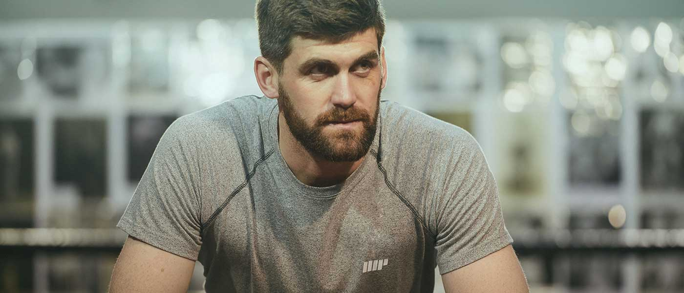Mannelijke geschiktheid model droeg een grijze myprotein t-shirt in de sportschool