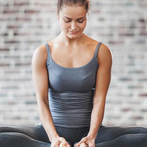Vrouw die zich uitstrekt in de studio sportschool zat met de voeten dicht bij elkaar