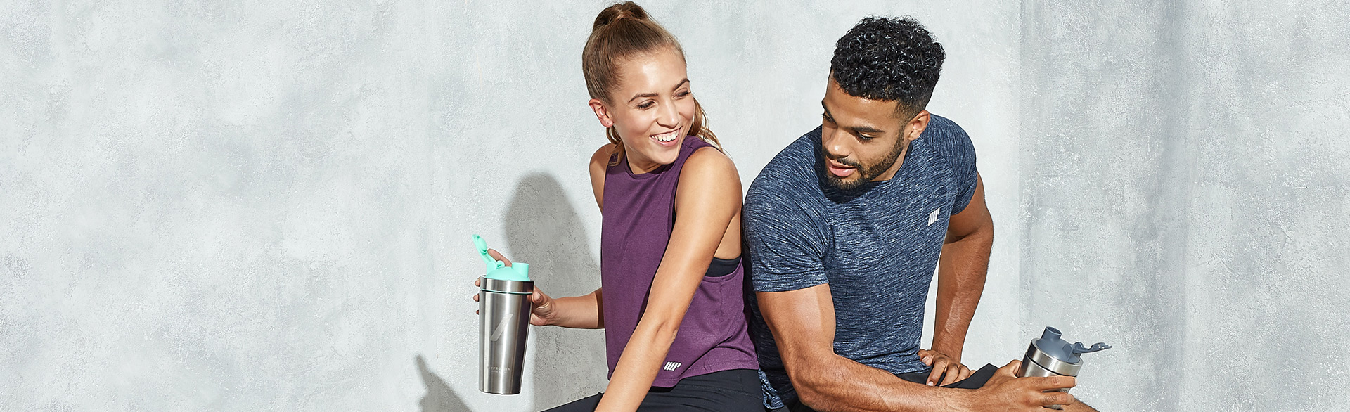 Man and woman drinking protein
