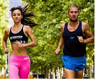 Samci a samice atleti jogging venku v myprotein sportovního oblečení