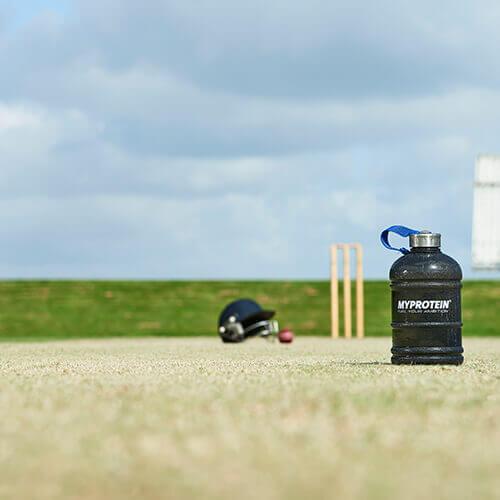 Cricket quipment s myprotein láhev napůl galonů vody v popředí