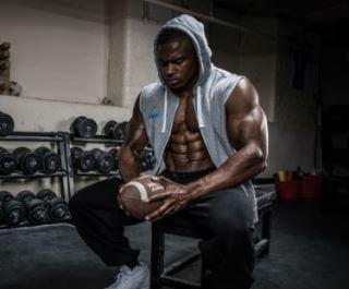 Amerikansk fodboldspiller hvile i træningscenter med fodbold