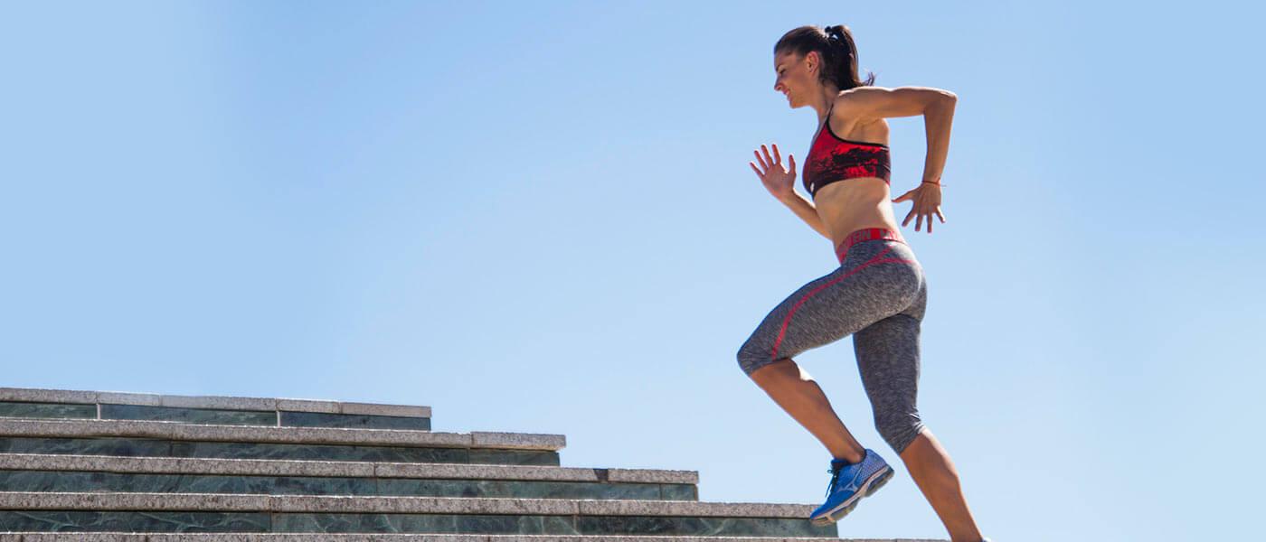 Kvindelige atlet kører op trin i myprotein sports-bh og leggings