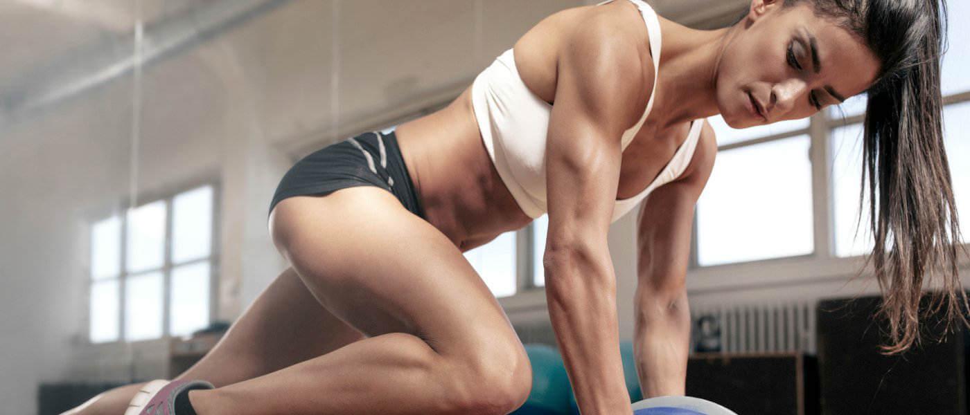 Tonet kvindelig atlet stretching i træningscenter med medicin bold