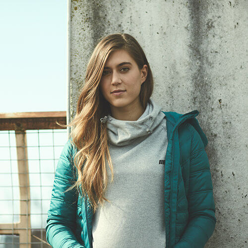 Kvindelige model fremvisning grå myprotein hættetrøje og let turkis puffer jakke