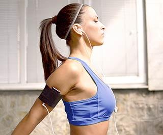 Kvinde strækker sig i gym lytte til musik