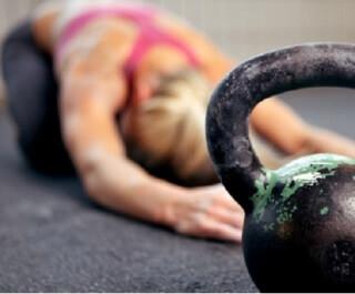 Kvindelige atlet stretching med kettlebells nærheden