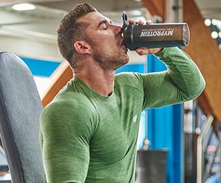 Mand fitness model i grøn myprotein ydeevne top drikke fra sort shaker flaske