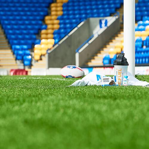 Myprotein uudelleen: polttoaine ravistin botle ja proteiini tonttu vieressä rugby pallo ja rajat baari Warrington rugby kentällä