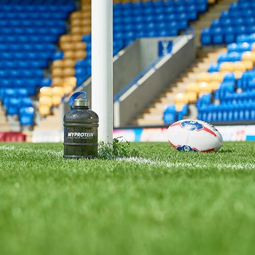 Myprotein puoli gallonaa Hydrator pullo vieressä rugby pallo ja poikittaispalkki rugby kentällä