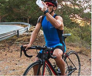 athléte de triathlon s'arrétant pour boire dans son shaker myprotein