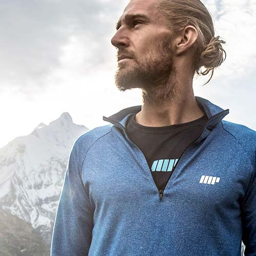 homme barbu dans les montagnes portant un sweat-shirt et un tee-shirt myprotein