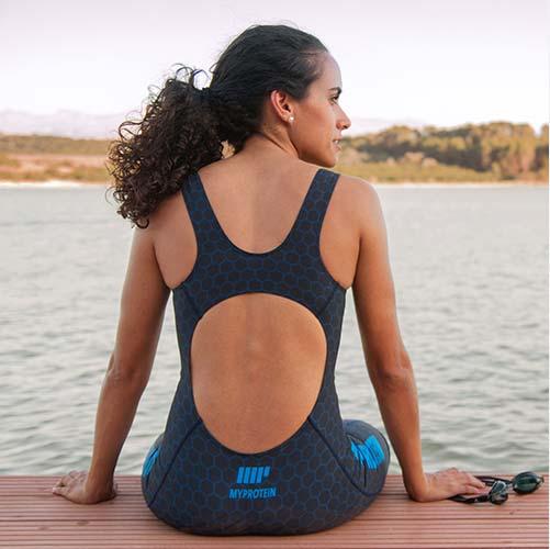 jeune femme portant un maillot de bain et des lunette de natation myprotein assise au bord de l'eau