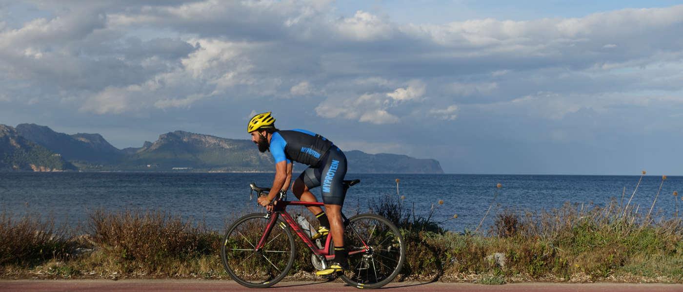 homme faisant du vélo au bord avec la mer et des montagnes en fond