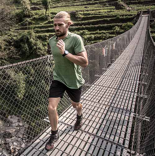 Muški sportaš trči preko mosta u zelenom myprotein sportske performanse majici