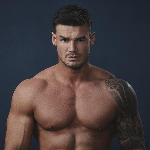 ragazzo bruno muscoloso con tatuaggi a torso nudo