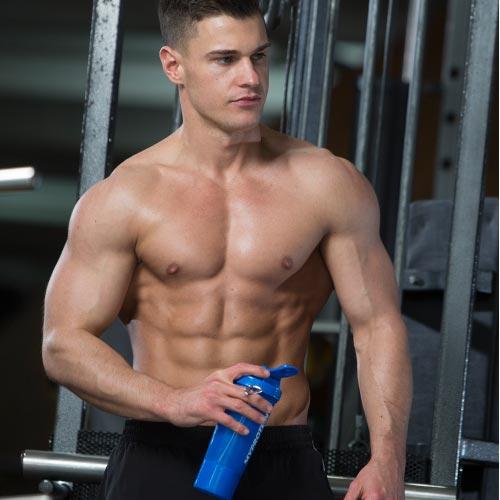 ragazzo muscoloso bodybuilder che si allena in palestra con shaker blu
